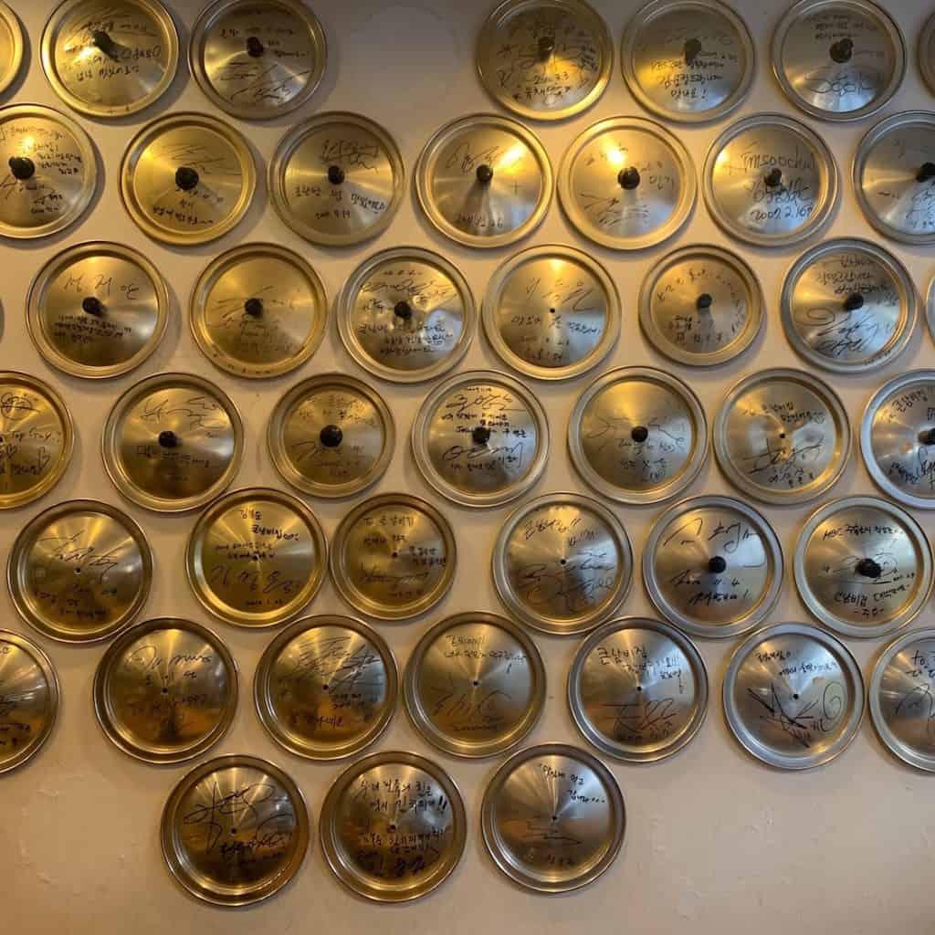 店内に飾られた鍋の蓋にはお店に訪れた芸能人のサインが。芸能事務所が近いこの土地ならでは。